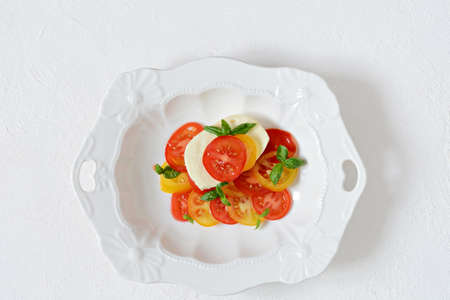 Caprese. Fresh colorful tomatoes and basil leaves in a ceramic bowl on a white background. Home made food. Concept for a tasty and healthy appetizer, flat lay. Zdjęcie Seryjne