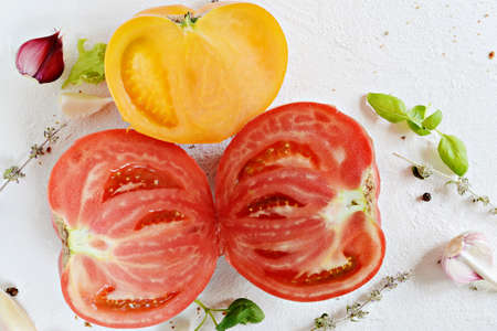 Ripe red and yellow tomatoes with garlic, basil, thyme and spices on a white background. Healthy eating concept.