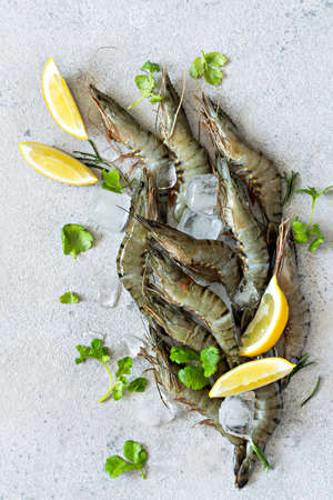 Fresh tiger prawns with lemon slices, herbs and spices on ice cubes on a light gray background. Raw marinated seafood ready to cook