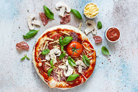 Cooking Italian pizza with tomato sauce, fresh tomatoes, cheese, mushrooms, salami slices and basil. Fresh food cooking concept at home. Semi-finished product, raw dough.