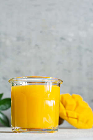 Fresh mango juice in a glass glass with mango slice on a gray background. Exotic drink, copy space. Trending colors of the year