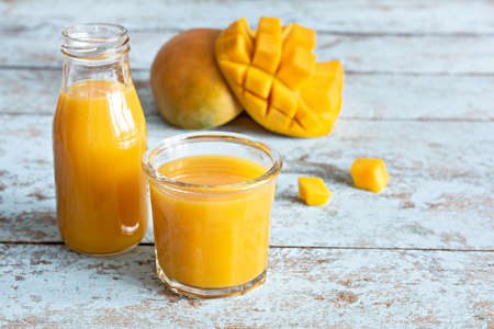 Fresh mango juice in a glass glass with mango slice on a blue wooden background. Exotic drink, copy space. Trending colors of the year Zdjęcie Seryjne