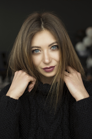 Girl with blue eyes. Woman posing in cafe. Wear black sweater.