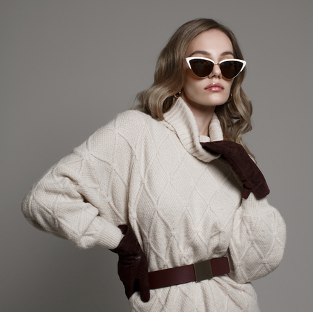 Fashion blonde model in white sunglasses, burgundy gloves, white sweater and curly blonde hair. Studio shoot.