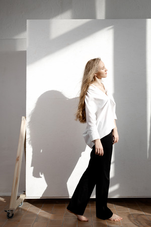 Beautiful fresh blonde model in white shirt and black trousers. Shadows on background