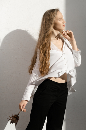 Beautiful fresh blonde model in white shirt and black trousers with flower in hand