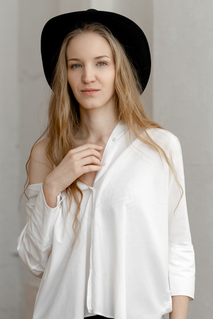 Beautiful thoughtful model  in black hat white shirt and black trousers