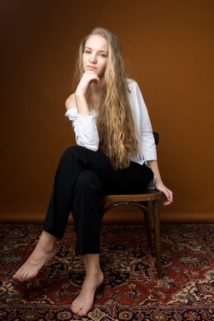 Beautiful model on orange background sitting on the chair in white shirt and black trousers