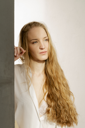 Charming blonde model with long hair in white shirt on white background